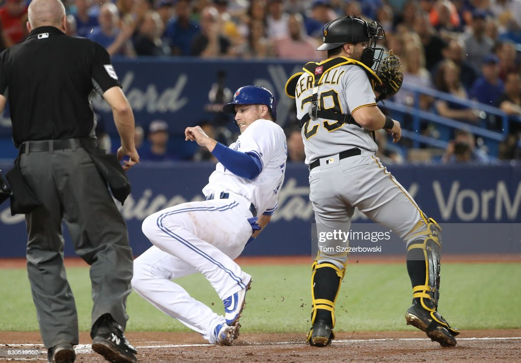 Justin Smoak #14 of the Toronto Blue Jays slides across home plate to score a run on a sacrifice fly in the second inning during MLB game action as Francisco Cervelli #29 of the Pittsburgh Pirates waits for the throw at Rogers Centre on August 11, 2017 in Toronto, Canada.