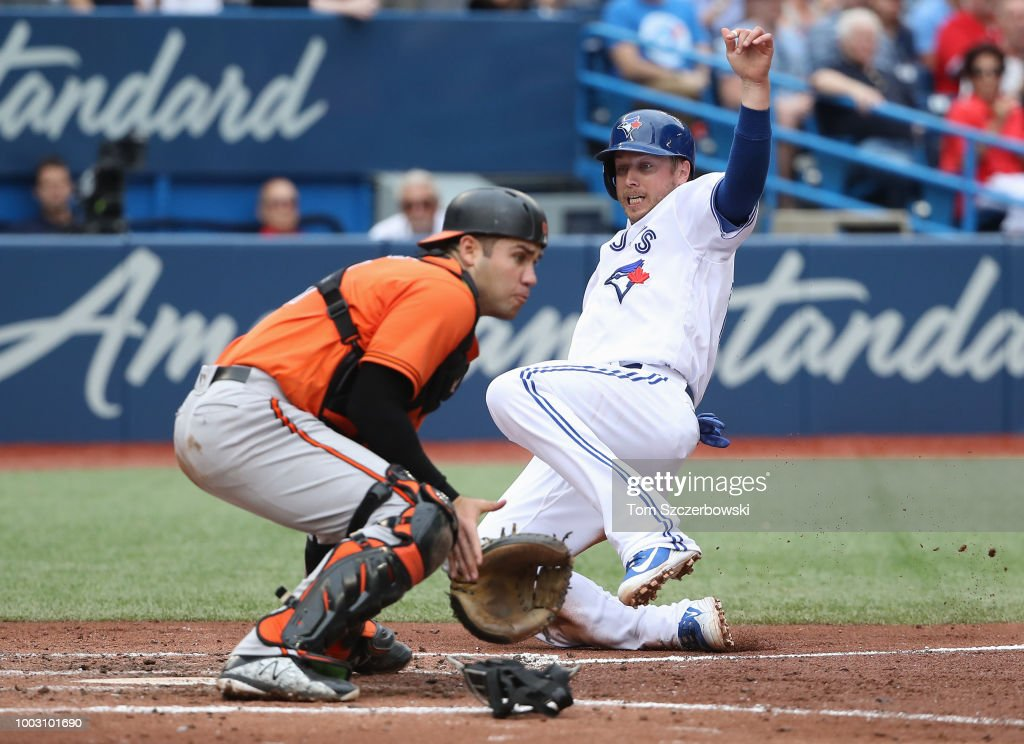 Justin Smoak #6 of the Toronto Blue Jays slides home safely to score a run as Austin Wynns #61 of the Baltimore Orioles cannot tag him out in the fourth inning during MLB game action at Rogers Centre on July 21, 2018 in Toronto, Canada.