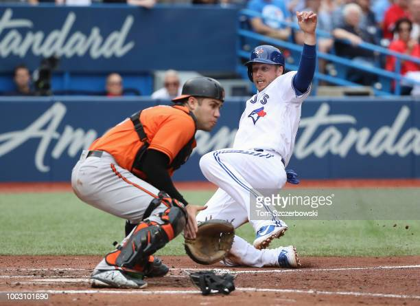 Justin Smoak of the Toronto Blue Jays slides home safely to score a run as Austin Wynns of the Baltimore Orioles cannot tag him out in the fourth...