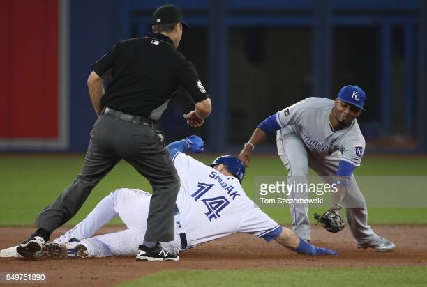 Justin Smoak of the Toronto Blue Jays slides into second base with a double in the first inning during MLB game action as Alcides Escobar of the...