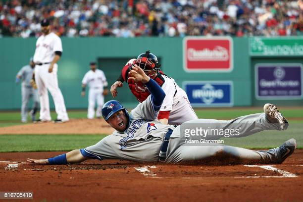 Justin Smoak of the Toronto Blue Jays slides safely under the tag of Christian Vazquez of the Boston Red Sox in the first inning of a game at Fenway...