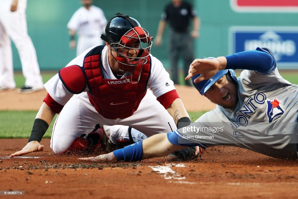Justin Smoak #14 of the Toronto Blue Jays slides safely under the tag of Christian Vazquez #7 of the Boston Red Sox in the first inning of a game at Fenway Park on July 17, 2017 in Boston, Massachusetts.