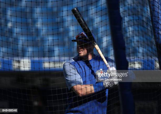 Justin Smoak of the Toronto Blue Jays swings a bat outside the batting cage as he warms up during batting practice before the start of MLB game...