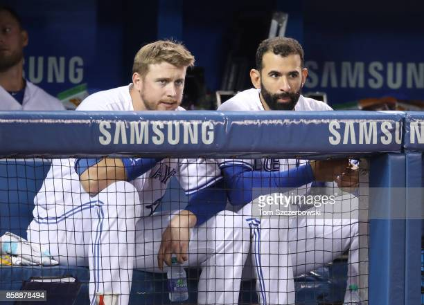 Justin Smoak of the Toronto Blue Jays talks to Jose Bautista as they look out from the top step of the dugout during MLB game action against the...