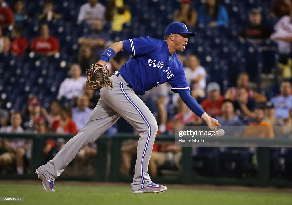 Justin Smoak #14 of the Toronto Blue Jays tosses underhand to first base in the ninth inning during a game against the Philadelphia Phillies at Citizens Bank Park on June 15, 2016 in Philadelphia, Pennsylvania. The Blue Jays won 7-2.