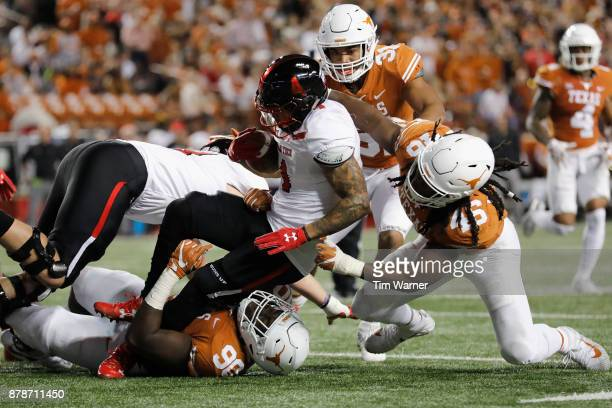 Justin Stockton of the Texas Tech Red Raiders is tackled by Charles Omenihu of the Texas Longhorns and Malik Jefferson in the second quarter at...