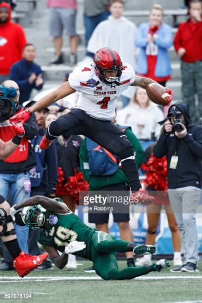 Justin Stockton of the Texas Tech Red Raiders leaps over Ronnie Hoggins of the South Florida Bulls in the first half of the Birmingham Bowl at Legion...