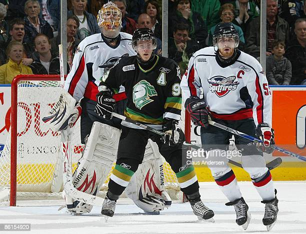 Justin Taylor of the London Knights looks for a shot to come in while standing between Andrew Engelage and Harry Young of the Windsor Spitfires in...