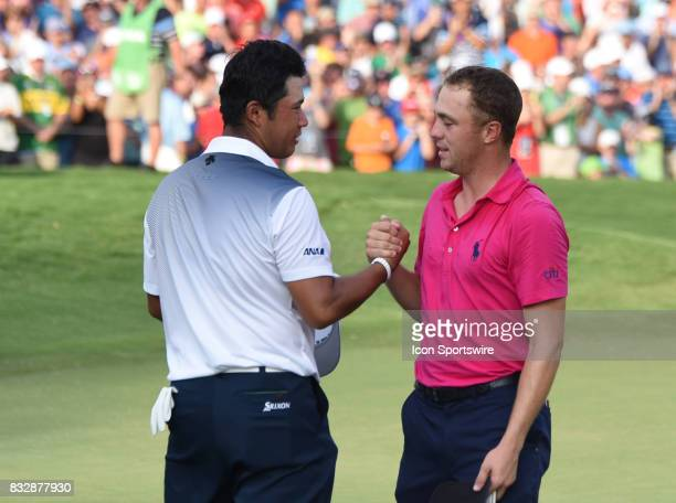Justin Thomas and Hideki Matsuyama clasp hands after the final round of the PGA Championship on August 13, 2017 at Quail Hollow Golf Club in...