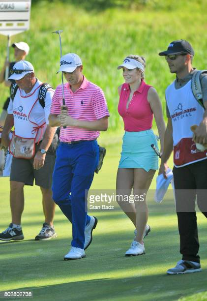 Justin Thomas and Paige Spiranac walk along the seventh hole during the ProAm round for the Quicken Loans National at TPC Potomac at Avenel Farm on...