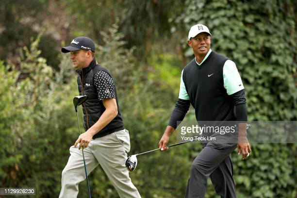 Justin Thomas and Tiger Woods walk off the 12th hole during the continuation of the first round of the Genesis Open at Riviera Country Club on...