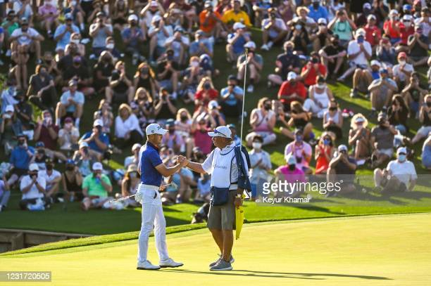 Justin Thomas celebrates with his caddie Jimmy Johnson after making his par putt on the 18th hole green as fans applaud during the final round of THE...