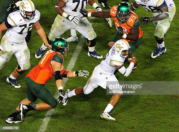 Justin Thomas of the Georgia Tech Yellow Jackets scrambles away from Anthony Chickillo and Calvin Heurtelou of the Miami Hurricanes at Bobby Dodd...
