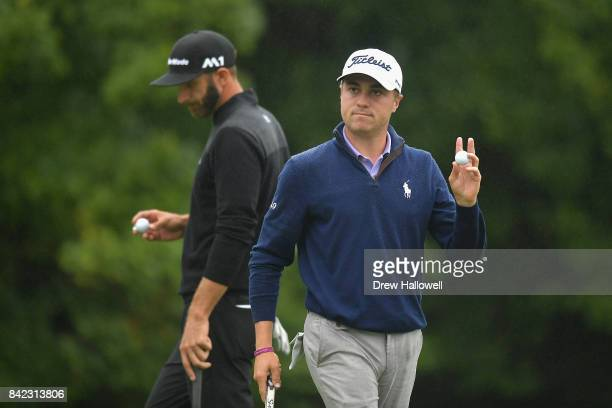 Justin Thomas of the United States acknowledges fans after putting on the 18th green as Dustin Johnson of the United States looks on during round...