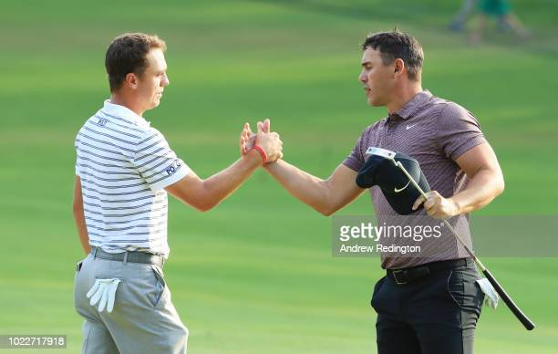 Justin Thomas of the United States and Brooks Koepka of the United States shake hands after finishing on the 18th green during the second round of...