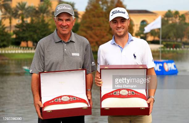 Justin Thomas of the United States and dad Mike Thomas pose with the trophy after winning the PNC Championship at the Ritz Carlton Golf Club on...