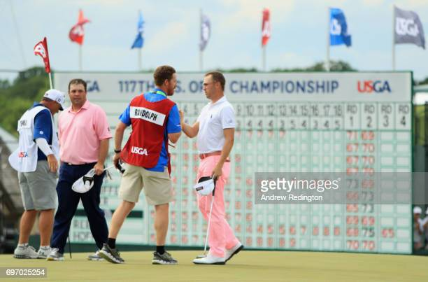 Justin Thomas of the United States and David Dubord caddie for Jonathan Randolph of the United States meet after finishing on the 18th green during...
