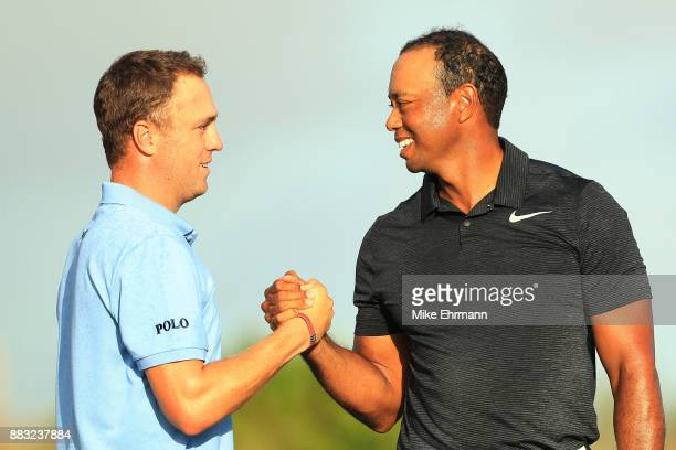 Justin Thomas of the United States and Tiger Woods of the United States shake hands after finishing on the 18th green during the first round of the...