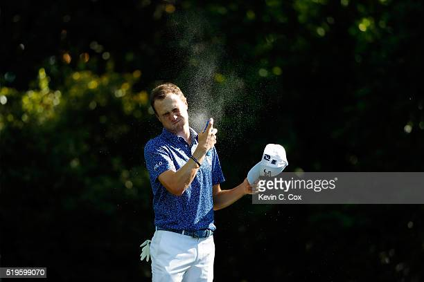 Justin Thomas of the United States applies sunscreen on the second tee during the first round of the 2016 Masters Tournament at Augusta National Golf...