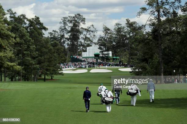 Justin Thomas of the United States Bill Haas of the United States and Marc Leishman of Australia walk down the seventh hole during the first round of...