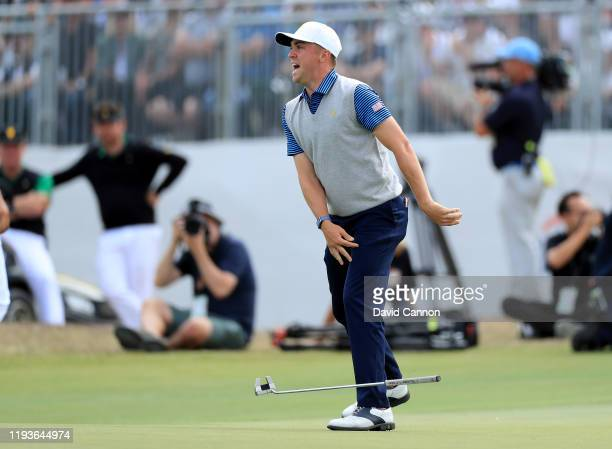 Justin Thomas of the United States celebrates after holing a birdie putt on the 18th green to win his match with Tiger Woods against Hideki Matsuyama...