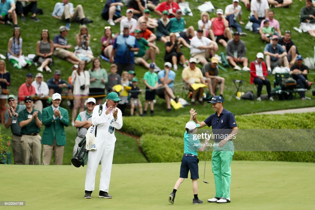 Justin Thomas of the United States celebrates with a young patron on the eighth hole during the Par 3 Contest prior to the start of the 2018 Masters Tournament at Augusta National Golf Club on April 4, 2018 in Augusta, Georgia.