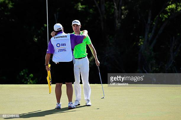 Justin Thomas of the United States celebrates with caddie Jimmy Johnson after winning during the final round of the SBS Tournament of Champions at...