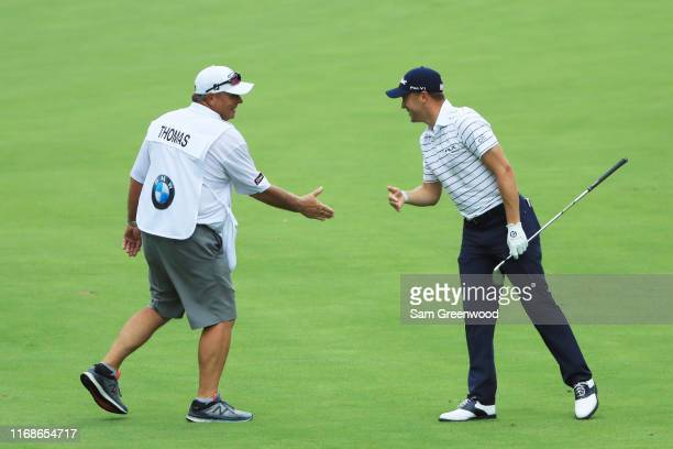 Justin Thomas of the United States celebrates with his caddie Jimmy Johnson after his eagle on the 16th hole during the third round of the BMW...