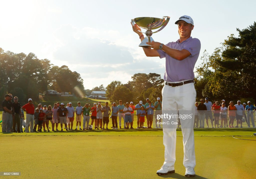 Justin Thomas of the United States celebrates with the trophy on the 18th green after winning the FedExCup and second in the TOUR Championship during the final round at East Lake Golf Club on September 24, 2017 in Atlanta, Georgia.