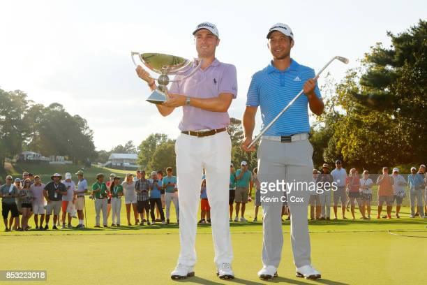 Justin Thomas of the United States celebrates with the trophy on the 18th green after winning the FedExCup and second in the TOUR Championship as...