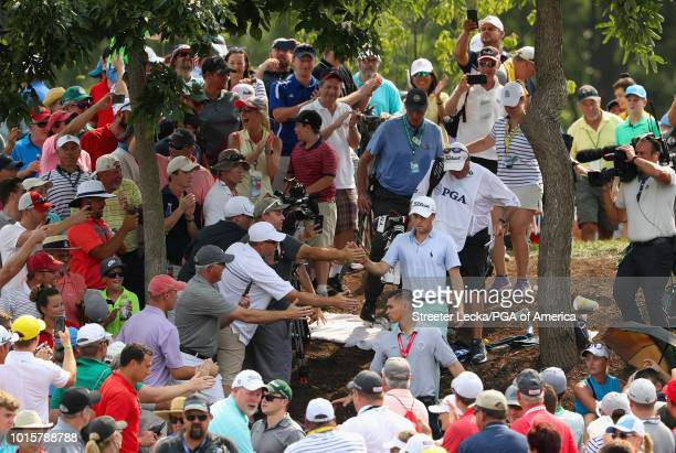 Justin Thomas of the United States high fives fans after playing a shot on the 11th hole during the final round of the 2018 PGA Championship at...