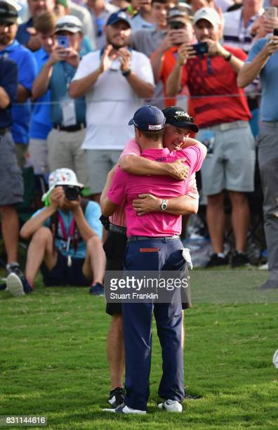Justin Thomas of the United States hugs his father Mike Thomas after finishing his round at 8 during the final round of the 2017 PGA Championship at...