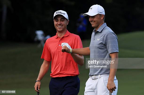 Justin Thomas of the United States is congratulated by Jordan Spieth of the United States after chipping in on the tenth hole during the first round...