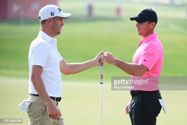 Justin Thomas of the United States of America and Rory McIlroy of Northern Ireland fist bump on the 9th green during Day One of the Abu Dhabi HSBC...