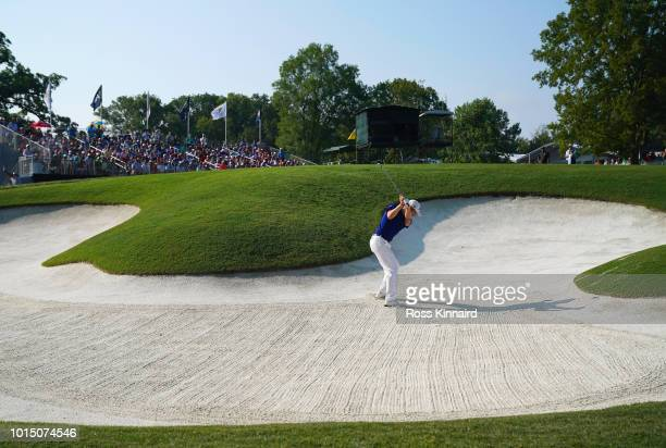 Justin Thomas of the United States plays a shot from a bunker on the 16th hole during the continuation of the weather delayed second round of the...