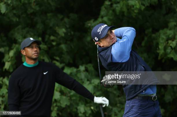 Justin Thomas of the United States plays a tee shot as Tiger Woods of the United States looks on during a practice round prior to the 120th U.S. Open...