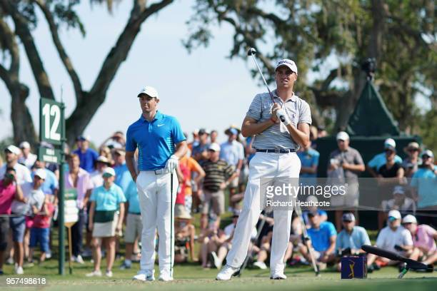 Justin Thomas of the United States plays his shot from the 12th tee as Rory McIlroy of Northern Ireland looks on during the second round of THE...