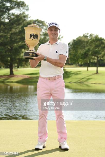 Justin Thomas of the United States poses with the trophy after winning the World Golf Championship FedEx St Jude Invitational at TPC Southwind on...