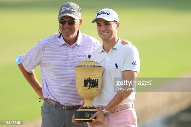 Justin Thomas of the United States poses with the trophy and his father, Mike Thomas, after winning the World Golf Championship-FedEx St Jude...