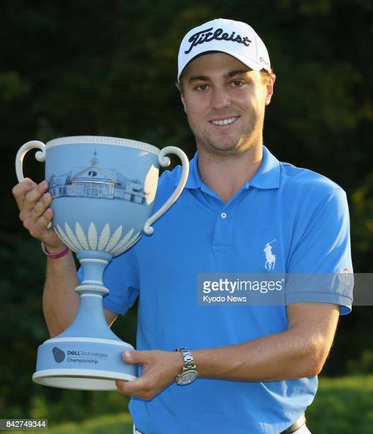 Justin Thomas of the United States poses with the victor's trophy after winning the Dell Technologies Championship at TPC Boston in Norton...