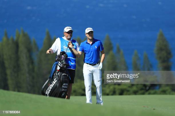 Justin Thomas of the United States pulls a club from his bag as he prepares to play a shot as caddie Jimmy Johnson looks on on the fourth hole during...