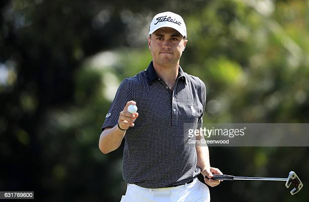 Justin Thomas of the United States reacts to his par putt on the first green during the final round of the Sony Open In Hawaii at Waialae Country...