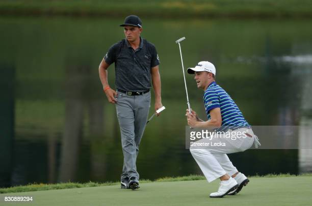 Justin Thomas of the United States reacts to his putt on the on the 17th green as Rickie Fowler of the United States looks on during the third round...