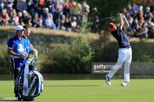 Justin Thomas of the United States team hits his second shot on the first hole in his match against Rory McIlroy of the European Team during singles...