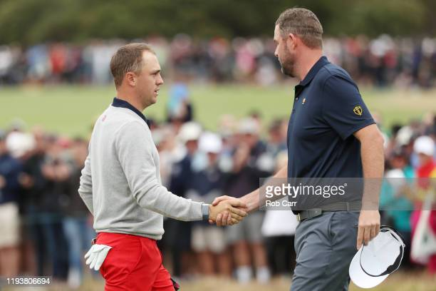 Justin Thomas of the United States team shakes hands with Marc Leishman of Australia and the International team 16 after Thomas and Rickie Fowler of...