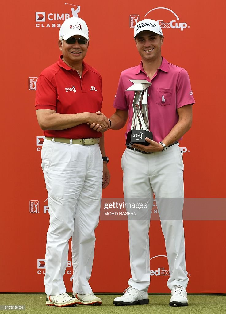 Justin Thomas of the US (R) shakes hands with Malaysia's Prime Minister Najib Razak (L) as they pose for pictures during the awards ceremony after Thomas's victory in the 2016 CIMB Classic golf tournament in Kuala Lumpur on October 23, 2016. / AFP / MOHD