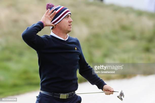 Justin Thomas of the US Team reacts after putting for birdie on the 14th green to go 2up with Daniel Berger over Jhonattan Vegas of Venezuela and the...
