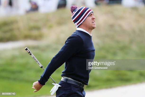 Justin Thomas of the US Team reacts after putting for birdie on the 14th green to go two up with Daniel Berger over Jhonattan Vegas of Venezuela and...