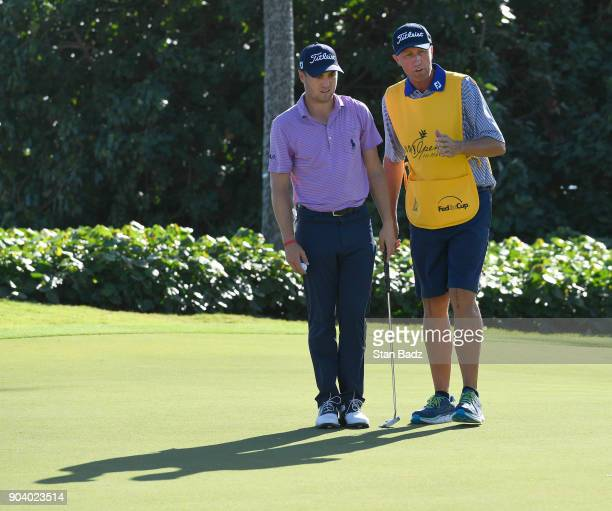 Justin Thomas stands with caddie Jim 'Bones' Mackay on the 11th green during the first round of the Sony Open in Hawaii at Waialae Country Club on...