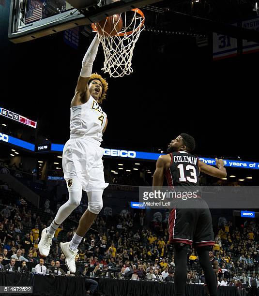 Justin Tillman of the Virginia Commonwealth Rams dunks the ball past Zach Coleman of the Massachusetts Minutemen in the quarterfinals round of the...